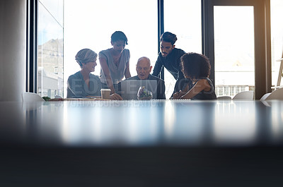 Buy stock photo Cropped shot of a diverse group of businesspeople using a laptop during a meeting in a boardroom