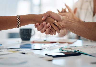Buy stock photo Cropped shot of two unrecognizable businesspeople shaking hands during a meeting in a modern office