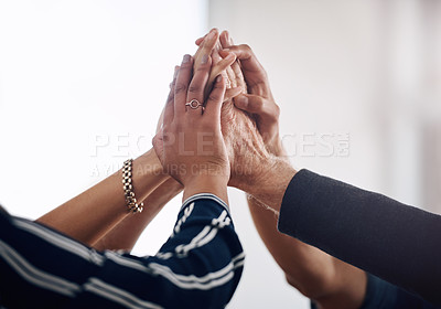 Buy stock photo Cropped shot of a group of unrecognizable businesspeople joining their hands together in unity while standing in a modern office