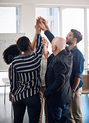 Buy stock photo Cropped shot of a diverse group of businesspeople joining their hands together in unity while standing in a modern office