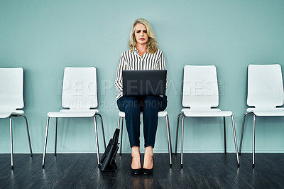 Buy stock photo Studio shot of a mature businesswoman using a laptop while waiting in line against a blue background