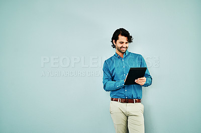 Buy stock photo Studio shot of a young businessman using a digital tablet against a blue background
