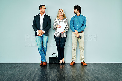 Buy stock photo Studio shot of a group of businesspeople standing in line against a blue background