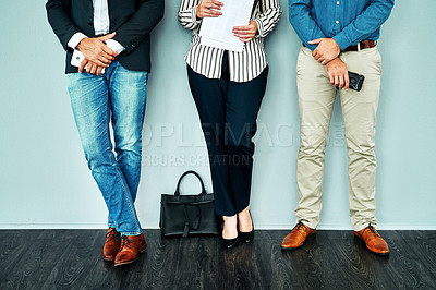 Buy stock photo Cropped studio shot of a group of businesspeople standing in line against a blue background