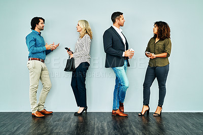 Buy stock photo Studio shot of a group of businesspeople having a conversation while waiting together against a blue background
