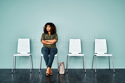 Buy stock photo Studio shot of a young businesswoman waiting in line against a blue background