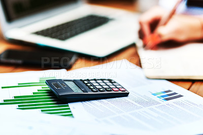 Buy stock photo Cropped shot of an unrecognizable businesswoman sitting and writing in a notebook after calculating her finances