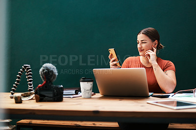 Buy stock photo Cropped shot of an attractive young businesswoman sitting alone at her desk and using her cellphone