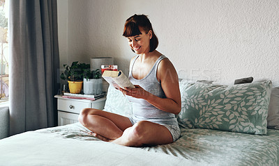 Buy stock photo Full length shot of an attractive young woman drinking tea and reading a book in her bedroom at home