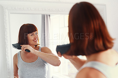 Buy stock photo Shot of an attractive young woman brushing her hair inside her bathroom at home