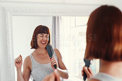 Buy stock photo Shot of an attractive young woman holding a hairbrush and singing in her bathroom at home