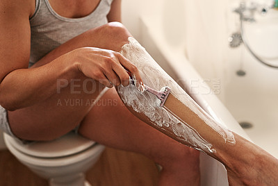 Buy stock photo Cropped shot of an unrecognizable young woman shaving her legs with a razor inside her bathroom at home