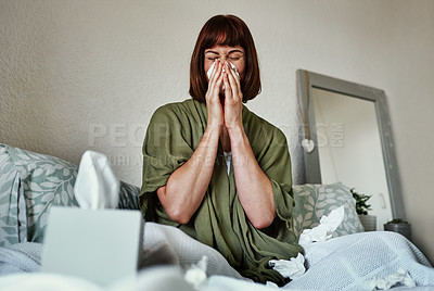 Buy stock photo Shot of an attractive young woman feeling sick and blowing her nose with a tissue inside her bedroom at home