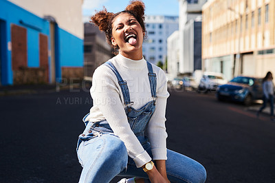 Buy stock photo Shot of a playful young woman out in the city during the day