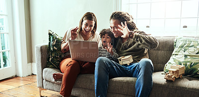 Buy stock photo Shot of a cheerful young couple and their son having a video call to relatives on a laptop while being seated on a sofa at home