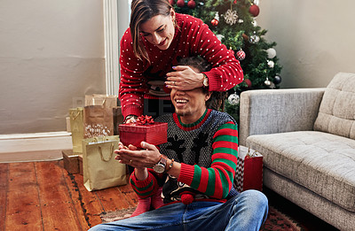 Buy stock photo Cropped shot of a cheerful young woman holding her husband's eyes closed while giving hime a present to open during christmas time at home