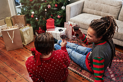 Buy stock photo High angle shot of a cheerful young couple enjoying a glass of wine together while being seated next to a christmas tree at home during the holiday season