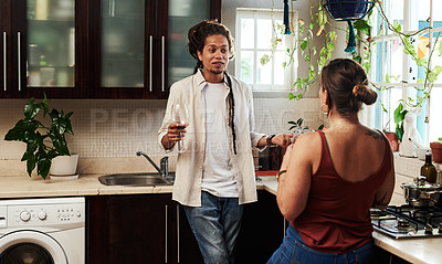 Buy stock photo Shot of a cheerful young couple enjoying a glass of wine together while standing in the kitchen at home