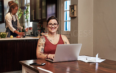Buy stock photo Portrait of a cheerful young woman working on a laptop and doing paperwork while being seated at a table at home
