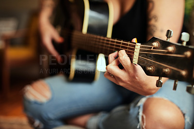 Buy stock photo Cropped shot of an unrecognizable woman playing a guitar at home