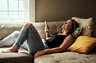 Buy stock photo Shot of a young woman using a smartphone and headphones on the sofa at home