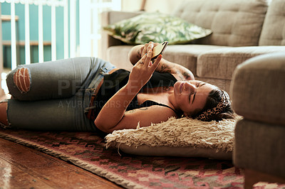 Buy stock photo Shot of a young woman using a smartphone on the floor of her living room at home