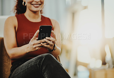Buy stock photo Cropped shot of an unrecognizable designer using her cellphone in her office