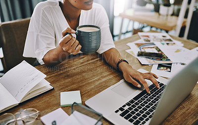 Buy stock photo Cropped shot of a businesswoman using a laptop and having coffee while working in her home office
