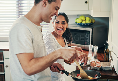 Buy stock photo Cropped shot of a happy young couple preparing breakfast together