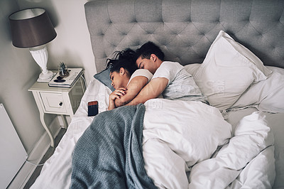 Buy stock photo Shot of a young couple sleeping together in their bed