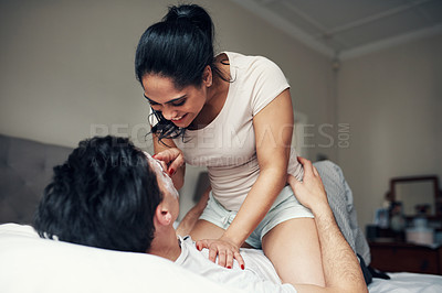 Buy stock photo Shot of a young man wearing a facial mask while lying on his bed with his girlfriend sitting on top of him