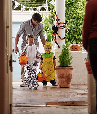 Buy stock photo Full length shot of a father and his adorable young sons trick or treating together on halloween