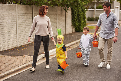Buy stock photo Full length shot of an adorable young family trick or treating together in the neighborhood on halloween