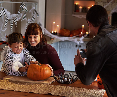 Buy stock photo Shot of a father taking pictures of his son and wife carving a pumpkin together on halloween at home
