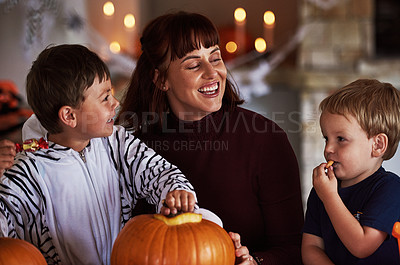 Buy stock photo Shot of two adorable little boys carving out pumpkins and celebrating halloween with their mother at home