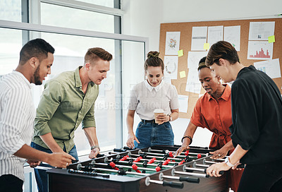 Buy stock photo Cropped shot of a diverse group of businesspeople standing together and bonding over a game of foosball in the office