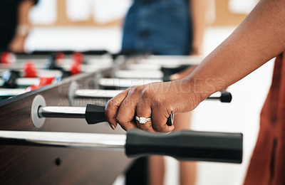 Buy stock photo Cropped shot of an unrecognizable businesswoman wearing a ring and ready to play a game of foosball