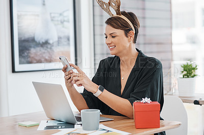 Buy stock photo Cropped shot of an attractive young businesswoman sitting and wearing christmas headwear while using her cellphone in the office