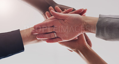 Buy stock photo Low angle shot of a group of unrecognizable businesspeople joining their hands together in a huddle in a modern office