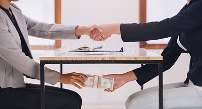 Buy stock photo Cropped shot of an unrecognizable female financial advisor receiving a bribe under her table while shaking hands with her client in her office