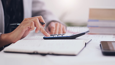 Buy stock photo Cropped shot of an unrecognizable businesswoman using a calculator and a notebook while  working on her finances in her office