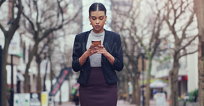 Buy stock photo Cropped shot of an attractive young businesswoman using a smartphone while walking outdoors in the city