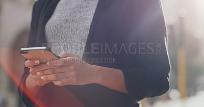 Buy stock photo Cropped shot of an unrecognizable businesswoman using a smartphone while standing outdoors in the city