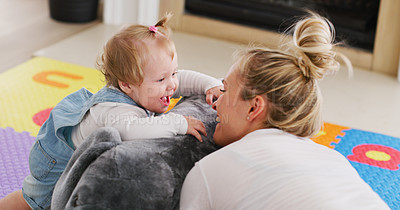 Buy stock photo Cropped shot of an affectionate young mother playing with her baby girl on the floor at home