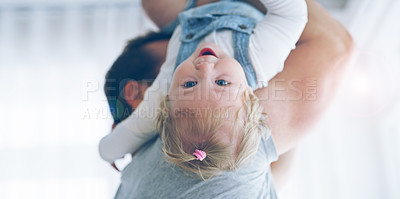 Buy stock photo Cropped shot of an unrecognizable father playfully lifting his little baby girl at home