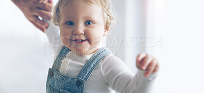 Buy stock photo Cropped shot of an adorable little girl learning to walk with her father supporting her at home