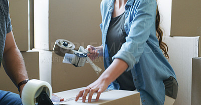 Buy stock photo Cropped shot of an unrecognizable couple using adhesive tape while packing up boxes on moving day