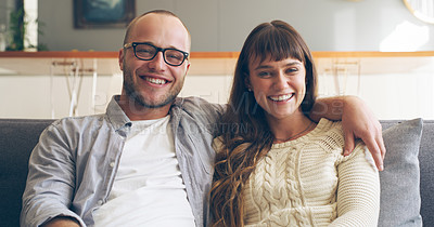 Buy stock photo Cropped portrait of an affectionate young couple smiling while sitting on their couch in their living room at home