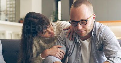 Buy stock photo Cropped shot of an affectionate young woman trying to talk to her upset husband while siting on a couch in their living room at home