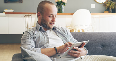 Buy stock photo Cropped shot of a handsome young man smiling while using a digital tablet in his living room at home